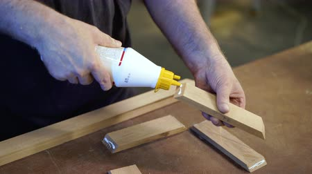 カーペンター : Unrecognizable carpenter applies glue to wooden parts. Handwork concept, woodworking workshop. Focus on hands.