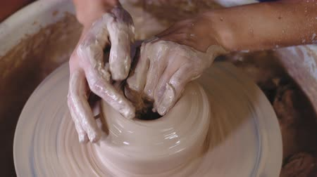 kalıp : Man works his hands with clay. Process of creating product from clay on potters wheel. Side view of artisan making pot or jug. Small business owner in workshop.