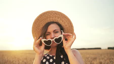 estilo livre : Portrait of stylish woman removes sunglasses in wheat field. Old fashioned girl in straw hat, black polka dot dress. Travel, fashion, nature concept