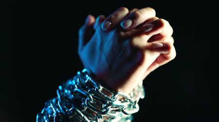 transação : Female bound hands of slave chained with iron chain on black background. Slavery, prisoner, violence concept.