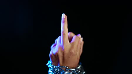 transação : Slave hands with metal chain on black. Shows aggressive gesture-middle finger. Fuck you, slavery, prisoner, violence concept.
