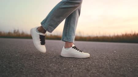 hajtások : Unrecognizable woman in jeans and white sneakers walks along on asphalt road ahead. Concept of modern shoes, travel, hiking in summer nature.Camera shoots from right side.