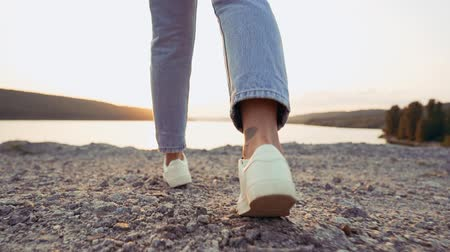 spor ayakkabısı : Girl in jeans and white sneakers walks ahead on rocky cliff to river. Concept of modern shoes, sunset, travel, summer nature.Camera shoots from behind Stok Video