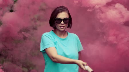 granada : Young pretty woman with pink smoke bomb or grenade in dramatic moody lighting. Girl in turquoise t-shirt and sun glasses making round movements.