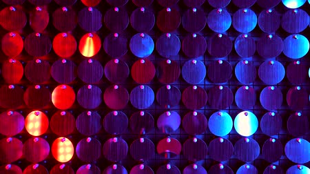 kinetik : Shiny kinetic surface panel illuminated by red and purple light in luxury boutique. Flickering background for interruptions or text savers. Mirror sequins sway by wind blowing.