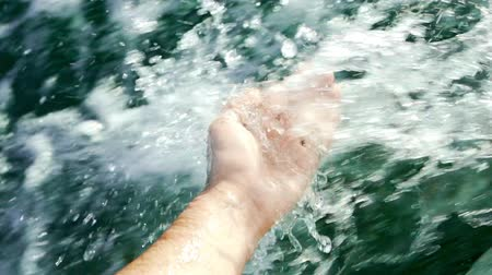 descobrir : Male hand touches clear river or sea water during summer boat or yacht ride