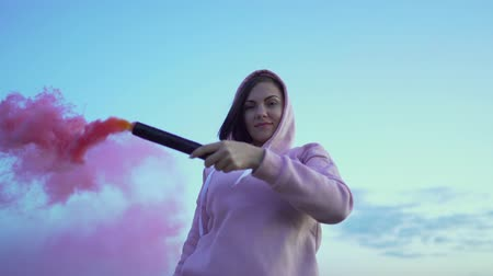 granada : Young pretty woman with pink smoke bomb or grenade on sunset sky background.
