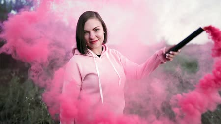 granada : Young pretty woman with pink smoke bomb or grenade in dramatic moody lighting