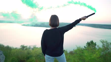 granada : Girl in black making round movements standing on rock above river. Young woman with green smoke bomb or grenade on dramatic nature background