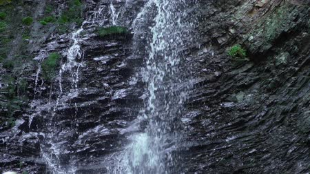 hdtv : Mountain waterfall flows down from forest cliff. Beautiful nature background. Stock Footage