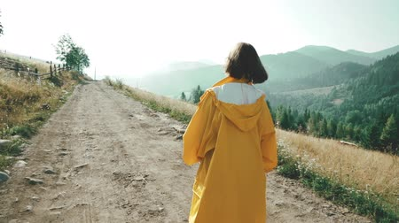 andar : Woman in yellow raincoat walking on village off road. Early morning nature in Carpathian mountains. Travel concept Vídeos