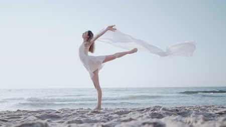 lépések : Flexible gymnast is dancing on ocean with huge silk fabric fluttering in wind.Ð¡oncept of tenderness, lightness, art and talent in nature