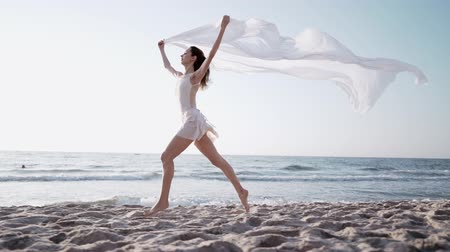 tüt : Young athletic girl running on ocean beach with huge silk fabric fluttering in wind.Ð¡oncept of tenderness, lightness, art and talent in nature