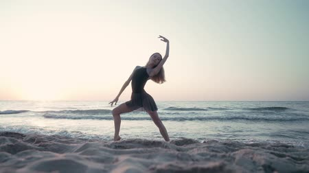 nőiesség : Young pretty ballerina in black dress dancing ballet on sea or ocean sandy beach in morning light. Concept of stretching, art, nature beauty