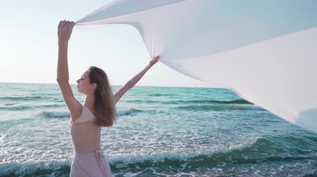 tiptoe : Close up of young woman holding long huge white silk fabric like sail on sea or ocean beach. Freedom, tenderness, travel concept.