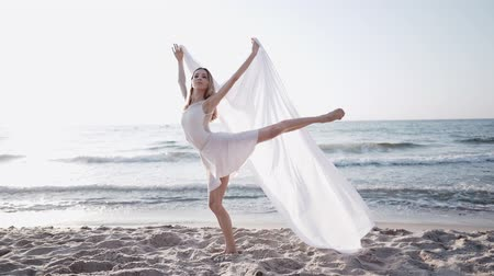 tiptoe : Dancing lady with white cloth on sea background. Nature, ballet, gymnastic concept. Woman dancer stretching. Amazing scene. Slow motion