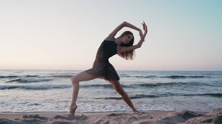 tiptoe : Dancing ballerina in black silk dress on embankment near ocean or sea at sunrise or sunset. Silhouette of young woman with long hair practicing classic exercises with emotions Stock Footage