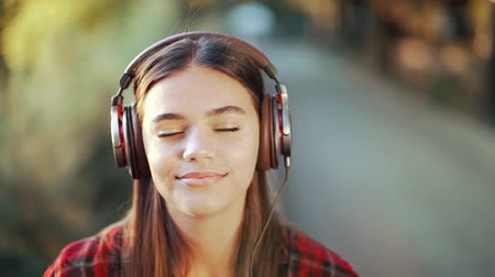 atitude : Young teenager listens to music through headphones in park.Girl in red plaid shirt smiles, dancing to rhythm.Concept of student life, freedom, modern youth Stock Footage