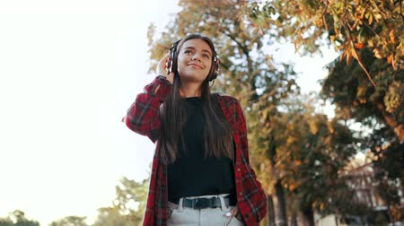 attitude : Portrait of attractive girl dancing with earphones in park. Woman smiling. moves to the rhythm.Friendly appearance of modern trendy hipster Stock Footage