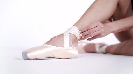 тапочка : Ballerina wraps white silk ribbons of soft top ballet shoes pointe and ties them up. Woman preparing for dance training lessons in gym.