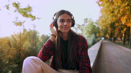 aparat ortodontyczny : Young teenager listens to music through headphones in park.Girl in red plaid shirt smiles, dancing to rhythm.Concept of student life, freedom, modern youth Wideo
