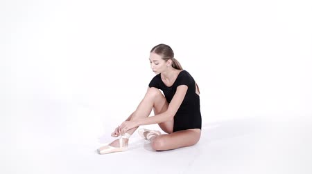 tüt : Ballerina wraps white silk ribbons of soft top ballet shoes pointe and ties them up. Woman preparing for dance training lessons in gym.