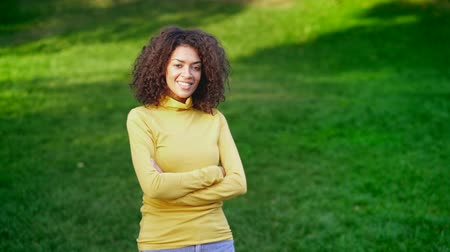 честолюбие : Portrait of beautiful mixed race woman with afro hair. Girl smiling on green grass background. Slow motion.