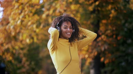 wearing earphones : African teenager girl listens to music with headphones in park. Cute woman in yellow, dancing with head, curly hair. Student, freedom, music concept.