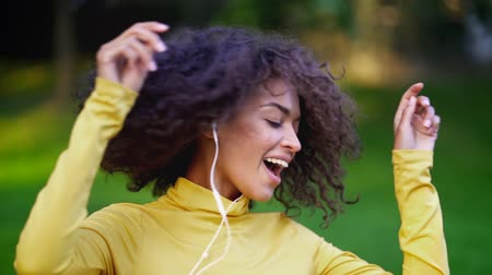 taniec : Close-up of african american girls head dancing in white earphones. Young woman with curly hairstyle in yellow enjoys music in park. Slow motion