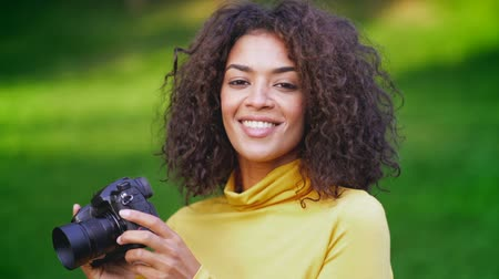 muhabir : Young pretty african woman in yellow takes pictures with DSLR camera over green background. Girl smiling, flirting and having fun as photographer.