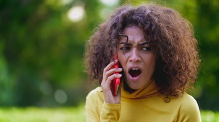 denying : Unsatisfied woman speaks on phone and expresses her disagreement. Denying, rejecting, disagree, portrait of african girl or student on green background Stock Footage