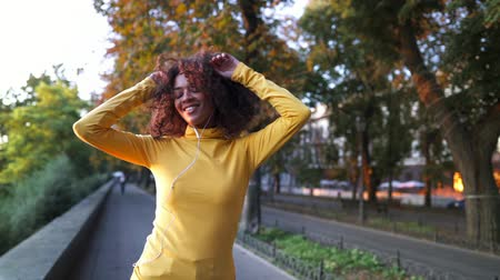 wearing earphones : Hipster in colorful yellow clothing walking and dancing on autumn urban street. Curly haired woman listens to music. Happy lifestyle concept