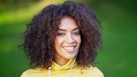 wearing earphones : Close-up of african american girls head dancing in white earphones. Young woman with curly hairstyle in yellow enjoys music in park. Slow motion