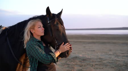 flexão : Blonde woman stroking and hugging horse. Beautiful lady with black stallion enjoying sunset nature. Love and friendship concept. Slow motion.