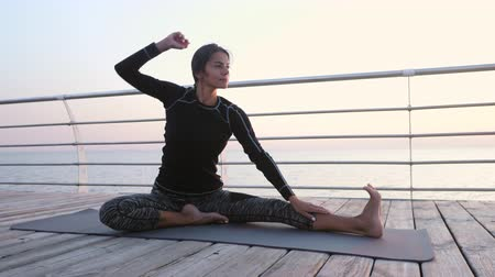 молодые женщины : Sports girl performs stretching exercises while sitting on black mat near sea in the morning. Healthy lifestyle concept