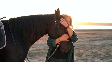 último : Blonde woman stroking and hugging horse. Beautiful lady with black stallion enjoying sunset nature. Love and friendship concept. Slow motion.