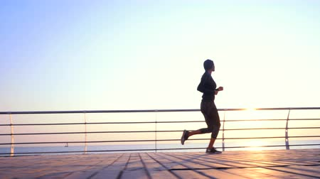 tracking : Athletic young girl jogging in the morning by sea wooden embankment. Silhouette of girl in sports costume. Beautiful sunlight. Healthy lifestyle concept Stock Footage