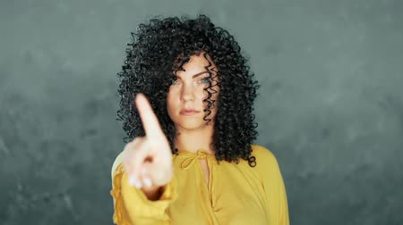 bastante : Woman with curly hair disapproving with no hand sign make negation finger gesture. Denying, Rejecting, Disagree, Portrait of Beautiful Girl. Body language