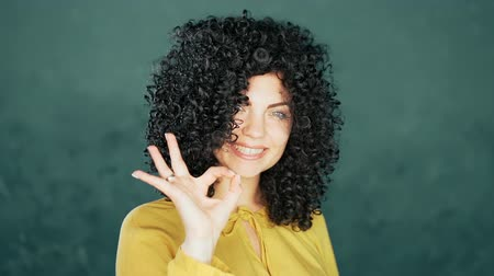 louvor : Young woman with afro curly hairstyle showing OK sign over blue background. Winner. Success. Positive brunette girl smiles for camera.