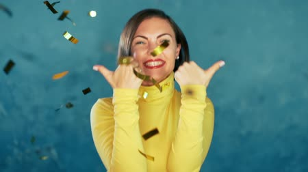 female hands : Surprised excited girl winning, showing thumbs up sign, having fun in confetti rain on blue background. Woman celebrating, depicts joy and happiness. Success, victory, holiday concept. Stock Footage
