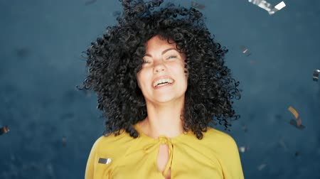 цели : Surprised excited girl with curly hair having fun in confetti rain on blue background. Woman celebrating, depicts joy and happiness. Success, victory, holiday concept.