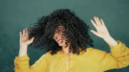 aluno : Beautiful woman with afro curly hair having fun smiling and dancing in studio against turquoise background. Music, dance concept, slow motion