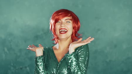 torcendo : Party dressed woman with red hair clapping hands over turquoise wall in studio. Slow motion. Concept of happiness, party, winning. Vídeos
