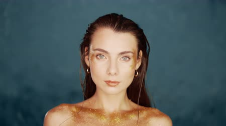 relance : Portrait of young beautiful model girl with original golden make-up and sparkles on blue background.Concept of haute couture, art visage, femininity