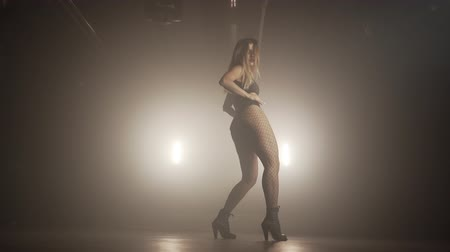 Young woman in black bodysuit with net pantyhose moves plasticly to music in dark room.Concept of sexual dancing,choreography,art.