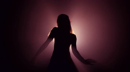Silhouette of beautiful dancer on smoky dark background.Spotlight shines back against sexy girl. She moving seductively.