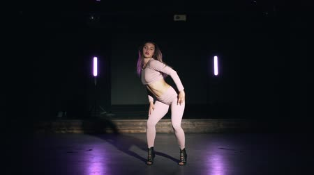 Portrait of beautiful girl in pink tight-fitting suit sensually dancing in dark studio with purple lamps.Concept of choreography, dance, performance