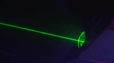 Glowing green laser beams at nightclub, concert or music festival. Night party atmosphere.