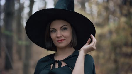 Portrait of young pretty witch in cap on autumn forest background. Halloween concept, cosplay dressing up. Slow motion Wideo