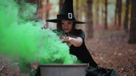 Black witch sits in front of cauldron from which green smoke is falling. Sorceress conjures, brews potion with spells. Horror, halloween, cosplay holiday, magic concept